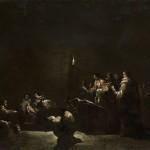 A dark scene of men performing a medical procedure.