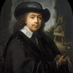 Self-portrait of a male artist wearing all black and a black hat, sitting in his studio.