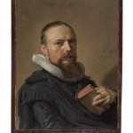 Portrait of an older man with a beard. He wears blue clothing and holds a book.