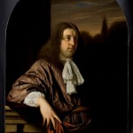 Portrait of a man with long brown hair leaning against a railing.