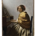 A girl sitting at a Virginal. She has curly hair and wears a yellow shawl.